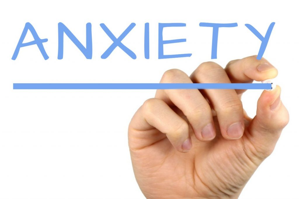 A hand writing the word anxiety.