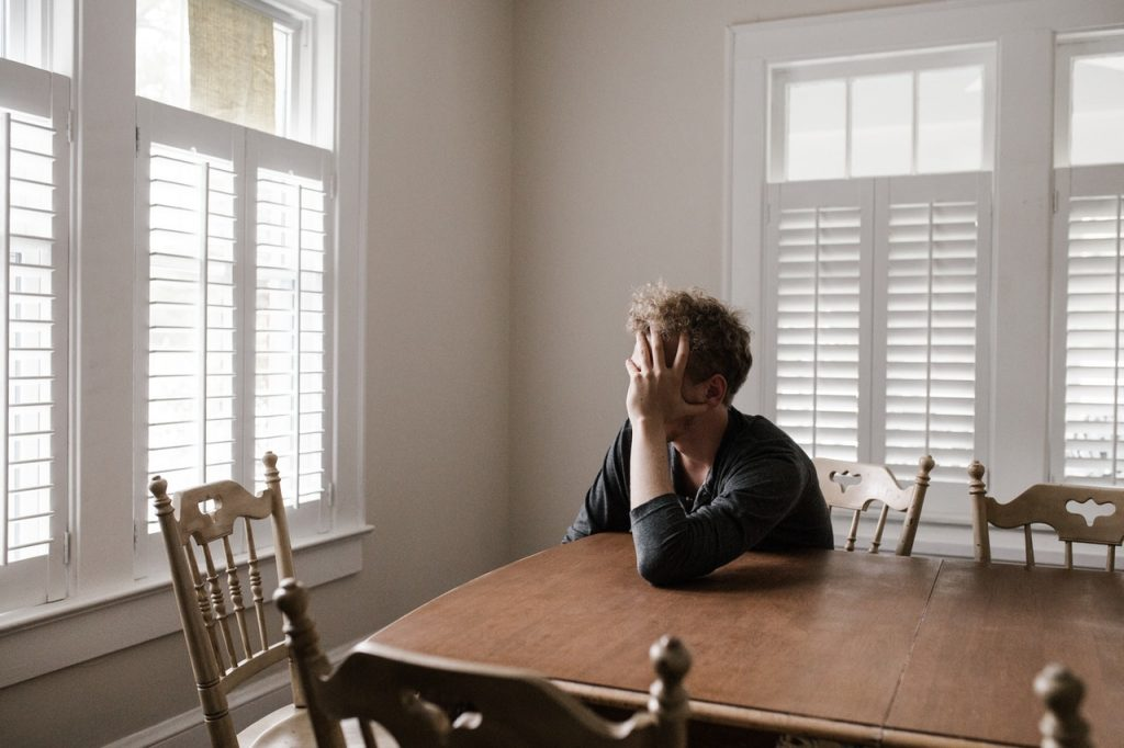 Anxious man looking out the window while sitting at the dinner table with hand on his face.