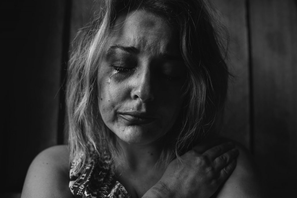 A woman crying looking anxious.