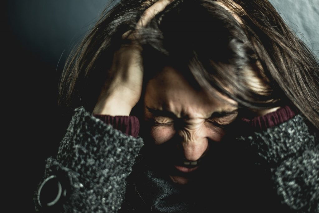 Woman holding her head with her eyes closed, looking scared or anxious.