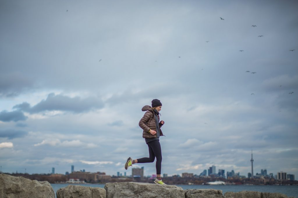 Woman with hoodie and beanie jogging.