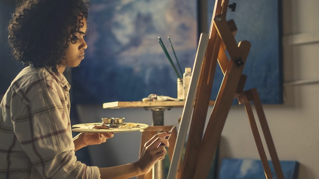 Woman wearing a white and brown long sleeved top. while painting.