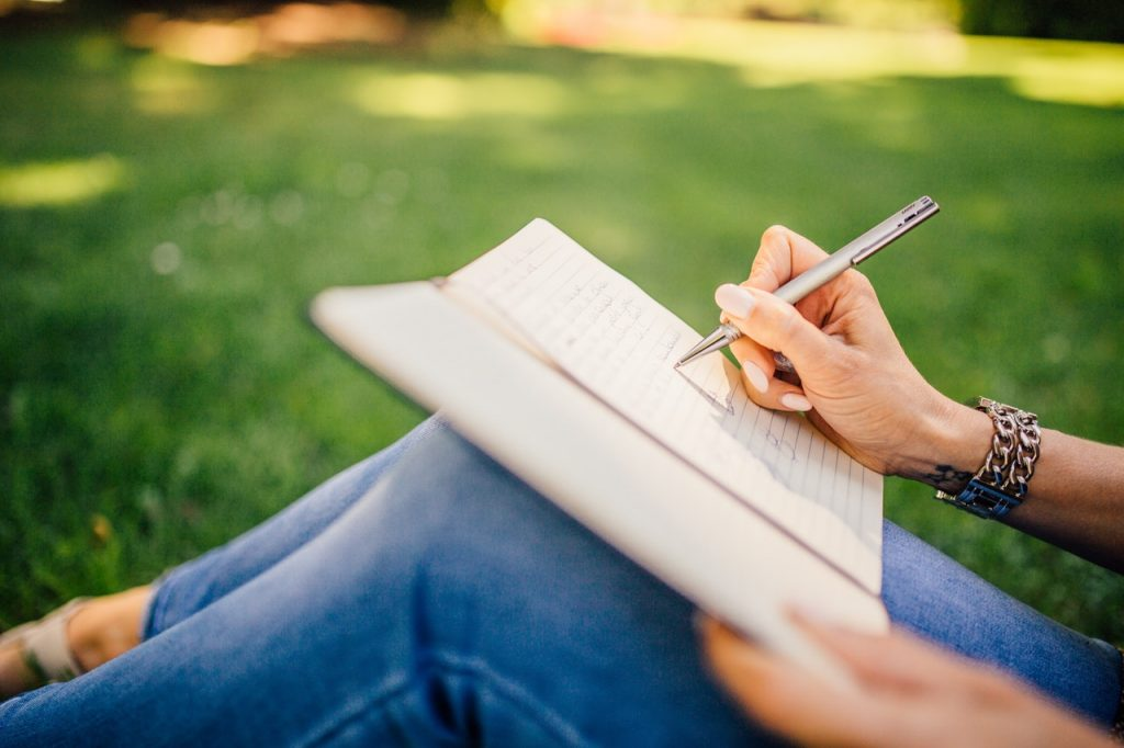 Woman writing on her notebook sitting on the grass.